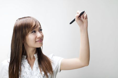 board marker: Closeup of young Asian business woman drawing on transparent glass or foil. Stock Photo