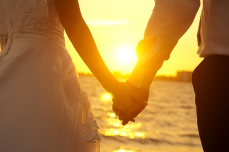 woman beach dress: Young adult male groom and female bride holding hands on beach at sunset.