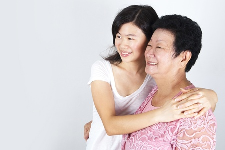 Senior Asian woman and young daughter looking away with smiling, on grey background. photo