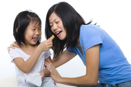 woman with ice cream: Little girl feeding her mum cone ice-cream.