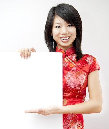 cheongsam: A smiling Oriental girl holding blank sign on grey background