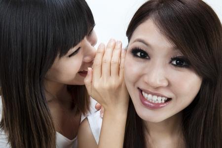 jokes: Two happy asian friends talking secretly over white background.