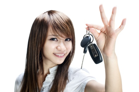 Young girl holding car key on white background photo