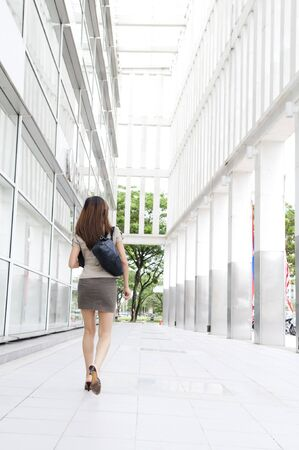 Rear view of Asian Businesswoman walking on street passing by an office building. photo