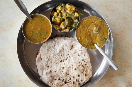 Traditional Indian cuisine vegetarian thali served in small bowls on a round tray. photo