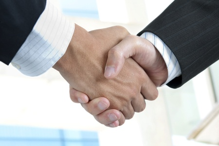 handskakning: Asian businessman handshake with modern skyscrapers as background Stockfoto
