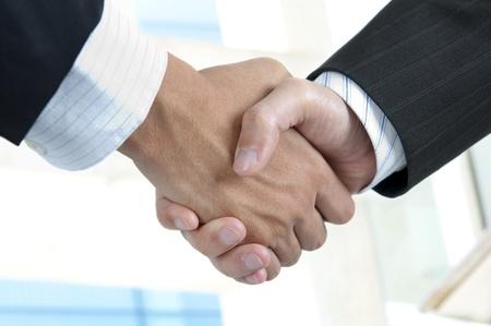 confianza concepto: Hombre de negocios asi�tica apret�n de manos con rascacielos modernos como fondo