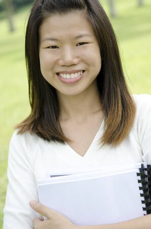 Asian college student smiling, standing at outdoor. photo