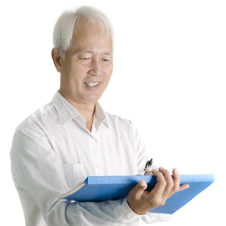 Asian senior businessman writing on document photo