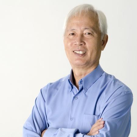 Crossed arms senior Asian businessman smiling on plain background Stock Photo - 8611397