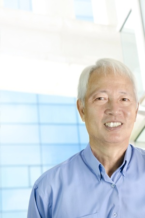 Portrait of an Asian  senior businessman standing in front modern building photo