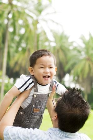 affectionate action: Un padre jugando con su hijo en un d�a de verano agradable. Foto de archivo