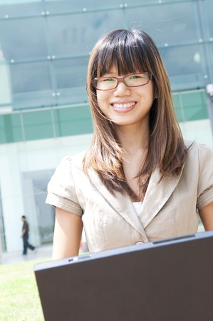 Asian student using laptop outside modern building photo