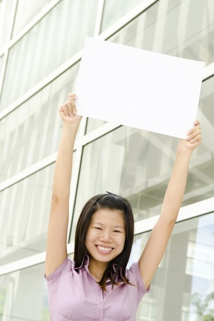 Beautiful businesswoman with blank paper for advertisement photo