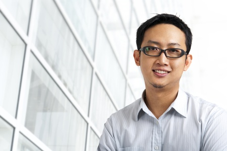 Good looking Asian standing outside office building photo