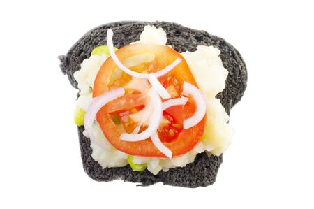 Black charcoal sandwich topped with mashed potato, tomato and onion. photo