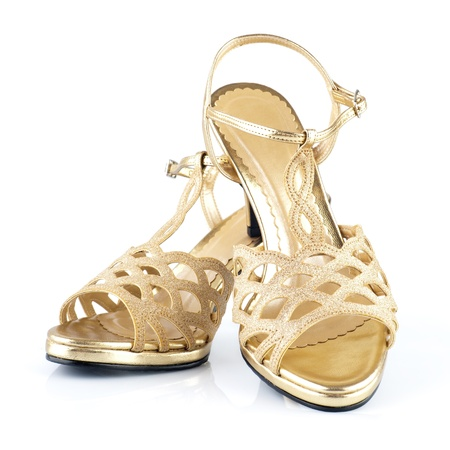 Pair of high heels golden female shoes isolated on white background photo