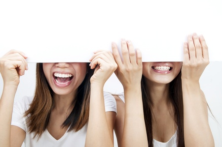 girls holding hands: Concept photo of Asian women holding a white card, covering eyes.