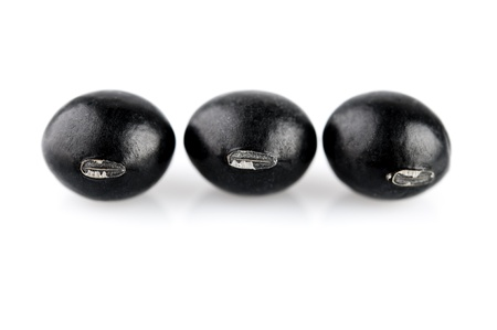 Three dried black beans isolated on white background. photo
