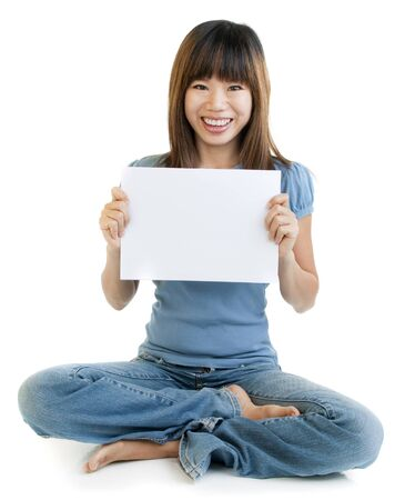 Asian sitting on floor holding blank paper for advertisment, with cheerful expression. photo