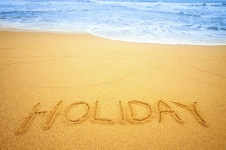 Holiday written in the sand on the beach blue waves in the background photo