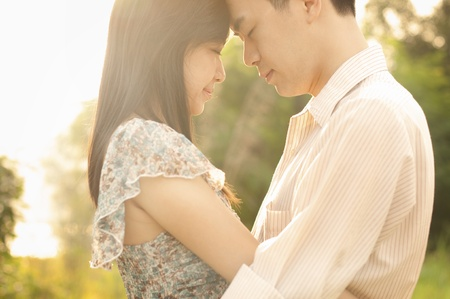 lovers park: Young couple in love, face to face in sunset