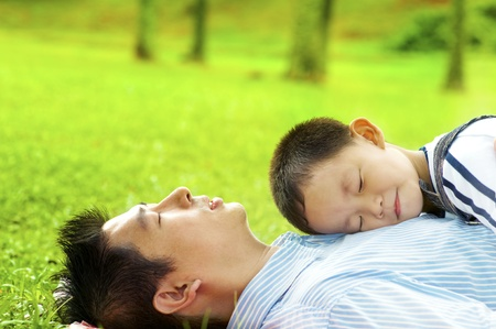 Boy lying on father. Father lying on green grass outside. photo