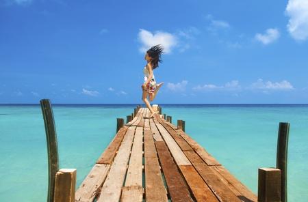 salto largo: Bastante joven es saltar hasta en el aire en el embarcadero de playa