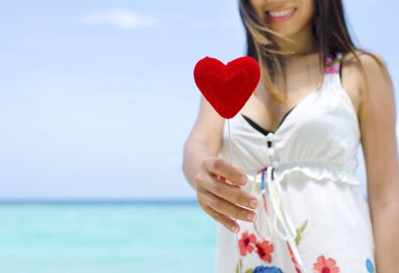 Portrait of a smiling young woman holding a heart shape at beach photo