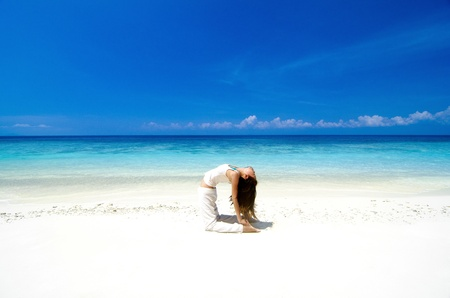 Woman practicing Yoga(Camel Pose) on the beach. photo