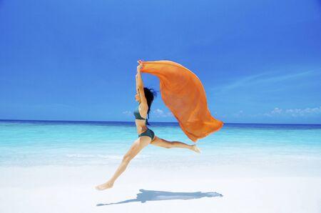 scarf beach: Chica muy joven bikini es saltar hasta en el aire en la playa