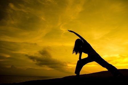 fortaleza: Silueta de mujer practicar Yoga (Pose de Guerrero) Foto de archivo