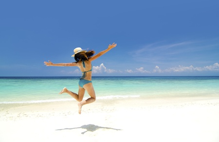 arms in air: Bikini young girl is jumping up in the air at the beach Stock Photo
