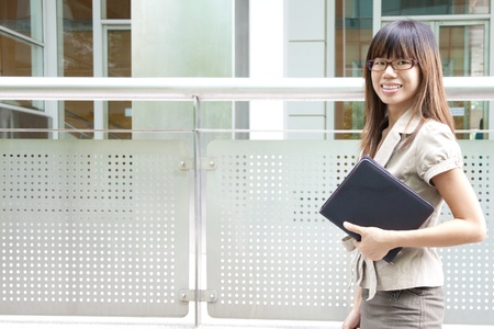 Education  Business woman passing by office building photo