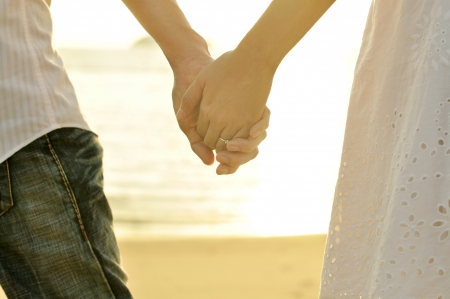 wives: Young adult male and female holding hands on beach at sunset. Stock Photo