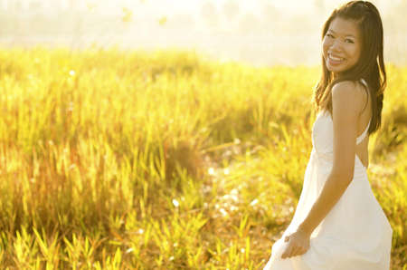 Asian bride at outdoor in a morning surrounding by golden sunlight photo