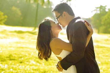 Bride and groom kissing in the park, back-lit in the morning. photo