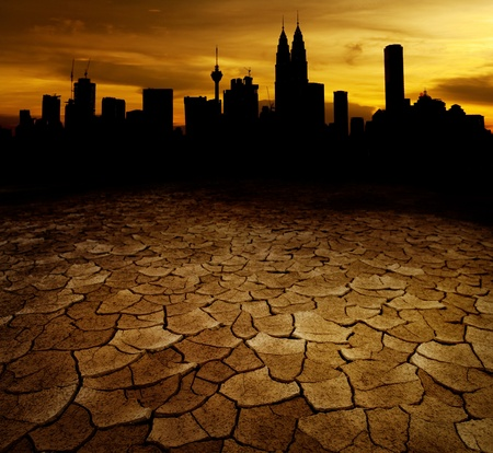 environmental issues: A city looks over a desolate cracked earth landscape in sunset
