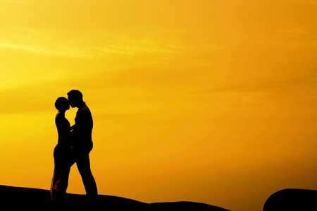 Silhouette of couple kissing in sunset photo