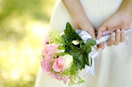 Bride holding her bouquet behind her back