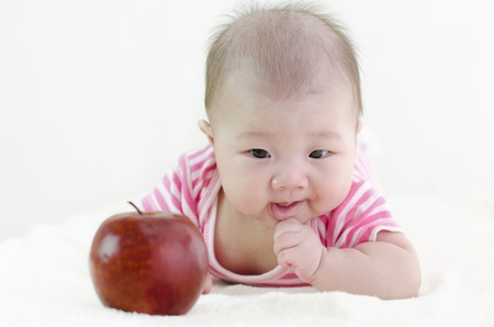 Asian baby girl trying to grab a large apple, focus on baby photo