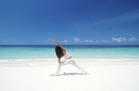 Woman practicing Yoga (Warrior Position) on the beach. photo