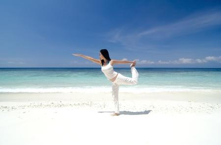 Woman practising Yoga (Warrior Position) on the beach. photo