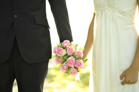 groom and bride: Outdoor Bride and Groom holding flower bouquet Stock Photo