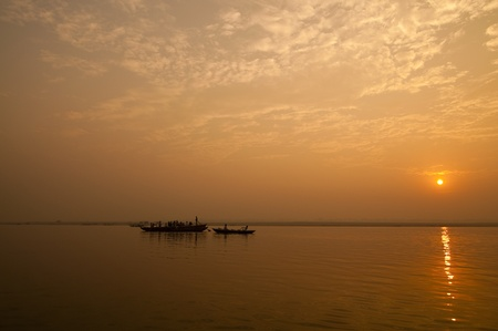 A stunning sunrise looking over the holiest of rivers in India. The Ganges. Silhouettes of boats dapple the horizon. photo