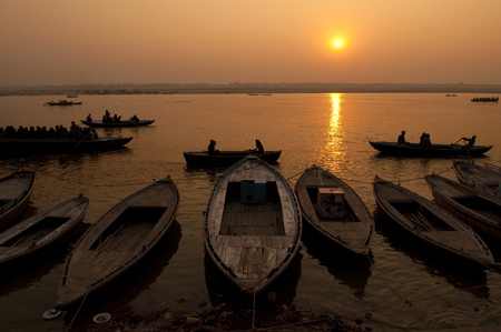 holiest: A stunning sunrise looking over the holiest of rivers in India. The Ganges. Silhouettes of boats dapple the horizon.