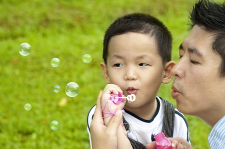 Asian father and son blowing bubbles outdoor photo