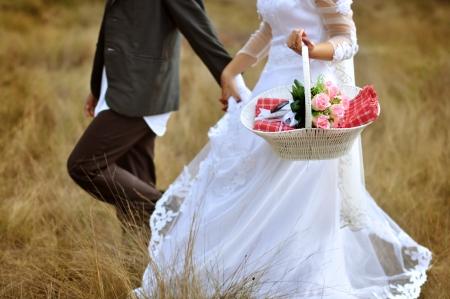 Bride and groom running on grassland