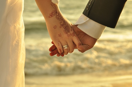 ring stand: Young adult male groom and female bride holding hands on beach at sunset.