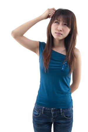 wondering: Cute Asian girl thinking hard, scratching head and looking up on white background. Stock Photo